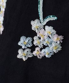 Extreme closeup of  pearlescent pink, white, and light blue sequins forming a floral design, that ornaments a black cocktail dress with net overlay from 1959 by Sophie of Saks.