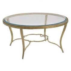 """Glass-topped coffee table with a gold-finished base and quatrefoil stretcher.    Product: Coffee tableConstruction Material: Metal and glassColor: Antique gold and silverFeatures:  Decorative stretcher1"""" Bevel edge Dimensions: 20"""" H x 40"""" Diameter"""