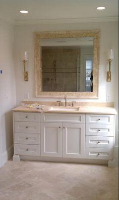 Limestone, white cabinets, visual comfort light, kohler purist, herringbone tile, tile mirror surround, his and hers vanity,