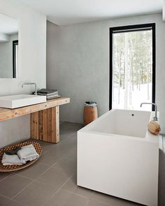 A large window bringing the outdoors in. Love the square profile of the bath and the rustic bench.    Finnish home created by two designers, Ulla Koskinen and Sameli Rantanen as a prototype for construction company Kannustalo.