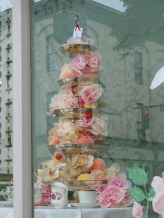 Storefront window filled with layers of flowers and fruit.