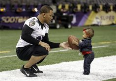 Baltimore Ravens running back Ray Rice, left, hands a football to his daughter, Rayven, age 1, after an NFL Super Bowl XLVII