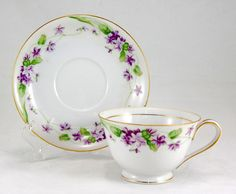 "Noritake ""NANCY""  Footed Cup and Saucer Set 2.25 in. Purple Flowers Gold Trim"