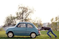 A woman pushing a car while the dog is driving. Photograph: Alessandro Bianchi