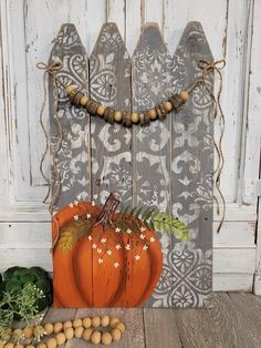 """24"""" Tall x 13.75"""" wide Are you looking for a unique, Fall decoration or a personal gift for the holidays? The handmade wooden bead and wood slice garland accents the reclaimed picket fence. The modern, free form stencil design gives this painting an interesting appearance. The pumpkin, fern and tiny flowers are hand"""