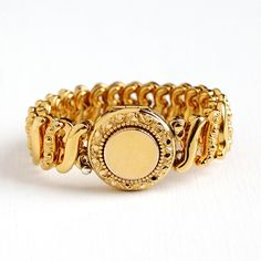 Beautiful and bright vintage gold filled expansion bracelet, featuring a center locket compartment. The center locket compartment opens up to reveal an empty interior, ready for your special photograph. The bracelet contains beautiful and detailed repousse designs, with S shaped