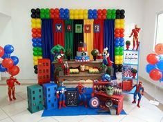 Decoração Vingadores Inclui 2 mesas 1 Escadinha de chão 5 bonecos 1 kit de bandejas 2 caixotes 4 vasos com buxinhos 1 de de quadrinhos 1 kit de cortinas coloridas 1 suporte Bexigas 1 kit de máscaras e escudo dos vingadores 3 prédios 1 bolo fake