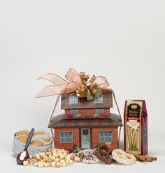 A warm and welcoming container. This two piece cottage home is great for many occasions; new home, hostess gift and to bring holiday warmth and cheer.     Contents: Ginger snap and apple cookies, hot cocoa chocolate spoon,chocolate drizzled caramel popcorn, chocolate wafer roll cookies, Belgium chocolate covered pretzels.     Net Wt. 12 oz.     Overall dimensions: 10.25 x 8.5 x 9.5
