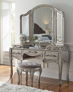 """Vanity with French-influenced decorative motifs. Rubberwood frame. Aged-silver patina finish. Three drawers. 62""""W x 20.5""""D x 34""""T. Imported. Boxed weight, approximately 92 lbs."""