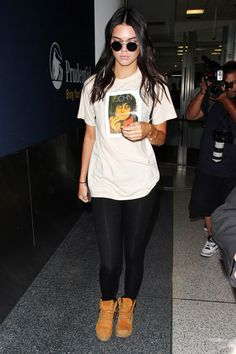 Kendall Jenner leaving LAX in a John Lennon tee, black leggings and Timberland boots.