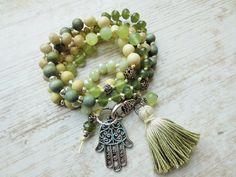 Wickelarmband: Perlen aus Jade, Glas und Holz sind kombiniert mit einer handgemachten Quaste und einer Hamsa Hand. Ein Einzelstück nur für Dich! Auch als Kette zu...