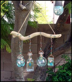 Garden art. Bottles I collected at thrift stores and a piece of driftwood I found. Copper wiring and some of my handmade lampwork beads too!