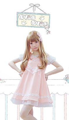 Sweetheart pink peach dress with a large heart shape breast decorated with embroidered flowers and white net. It is sleeveless with bow tie shoulder straps and the dress has shearing to the back and an underlining petticoat that peeks through the bottom of the dress. It is finished with a pretty row of white embroidered flowers around the hem.