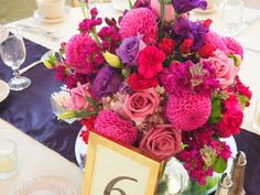 Pinks and purples make for a gorgeous contrasting centerpiece. Arrangement by Violets Event Floral Design in MA