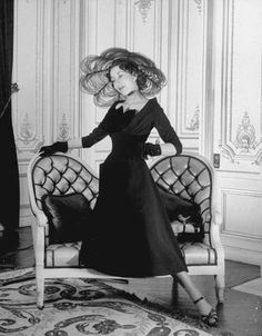 1947 Christian Dior Fashion Show, featuring a petal-shaped hat in transparent black with plain black dress.