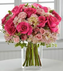 A delicate and sophisticated bouquet of sweet feminine flowers. Bright fuchsia roses are brilliantly eye-catching seated amongst pale pink spray roses and clouds of pastel pink hydrangea accented with floral greens. Elegantly situated in a clear...