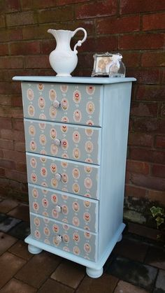 A splash of colour with duck egg blue and fronts of drawers covered in a floral fablon with diamante knobs added