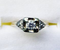 Circa 1940s late Art Deco or Retro engagement ring with an approximately 15 point old cut diamond surrounded by six single cut small diamonds