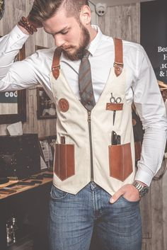Barber Vest in Canvas Cream Color with leather Pockets and Straps designed by Sweyn Forkbeard and 100% Handmade in London. Grey Cotton Lining, Brown Leather Cross Shoulder Adjustable Straps, Leather Pockets for your Tools, Brass Antique Accessories and the Sweyn Forkbeard logo engraved in leather.
