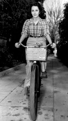 Through the Ages: Beauties on Bikes - Elizabeth Taylor: A young Taylor went for a slightly masculine look while cycling in the mid 1940s, pairing a plaid shirt with a pair of trousers and some lace-up oxfords. #InStyle