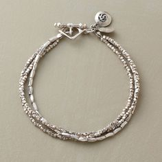 """SERENITY BRACELET--A triple strand of shimmering sterling silver beads culminates in a single satin-finished charm—the symbol for """"Om""""—the universal sound that bestows peace and tranquility. Toggle closure. Exclusive. 7-1/2""""L."""
