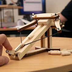 The ballista was an ancient artillery weapon that looked similar to a crossbow, but was more like a missile for the Greek and Roman Empires. Here's a desktop-sized one for the office.