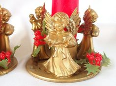 Vintage, gold, musical angels candle holders are decorated with sprigs of red and green plastic holly. In original box - handcrafted in Hong Kong.
