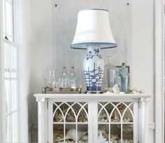A calm moment of coastal decor by Ralph Lauren Home. Complete with a favorite blue and white lamp atop a bookshelf filled with seashells and treasures from the ocean. Beach House Style, Beach House Decor, Home Decor, Seaside Style, Nautical Style, Beach Houses, Coastal Style, Sectional Furniture, Wicker Furniture