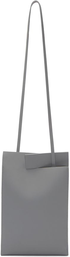 Matte leather tote bag in grey. Detachable and adjustable shoulder strap. Tab-slot closure at bag throat. 'Satin' finish at side panels. Suede lining. Tonal stitching. Approx. 8