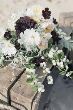 white green and black floral arrangement as centerpiece #weddingdecor #centerpiece #weddingchicks http://www.weddingchicks.com/2014/02/25/majestic-beach-wedding-ideas/