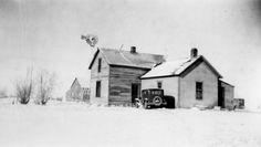 A plains farmstead in the middle of winter, Model T parked outside. 1920s.