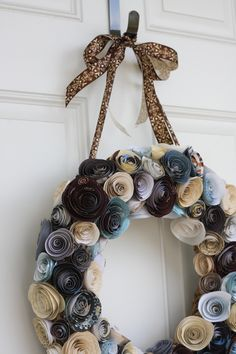 I was inspired by many of the fabulous paper flower wreaths out there on the web & decided (with the help of the paper flower tutorial at Jones Design Company) to give it a shot.  I love the way it turned out!