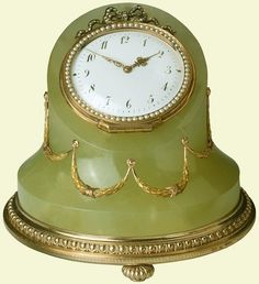 Fabergé desk clock of hoof form in carved bowenite, mounted in two-colour gold and silver-gilt foliate swags. Bezel of gold set half-pearls with rose diamond cresting bow, plain white-enamel dial with 12 hours represented in Arabic numerals fitted with pierced red-gold hands, gadrooned gold bun feet. Mark of Michael Perchin.