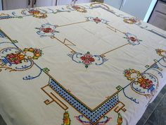 Heavy cotton, colorful cross-stitched tablecloth, 61x68. This light tan cloth was hand worked with a bold, colorful cross-stitch design. It will