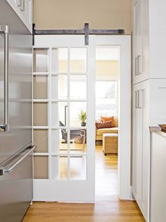 """Casual White Kitchen Smooth Transition """"The doorway to the living room offers a pleasant and practical surprise: a barn-style door that slides out from behind the refrigerator. Dining room sliding French door on track Style At Home, Barn Style Doors, Barn Doors, Wood Doors, Barn Door Designs, Pocket Doors, French Doors, Home Kitchens, Sweet Home"""