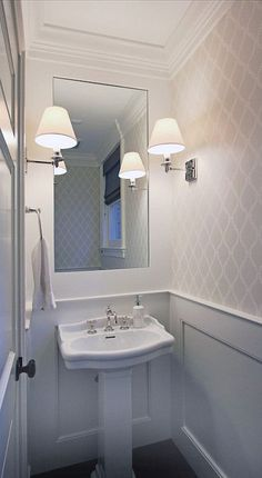 small powder room. white and light grey bathroom. crown moulding. Farrow & Ball Crivelli Trellis wallpaper. wainscoting on bottom half of walls. framing inset mirror. Alexa Hampton Abbot Single Arm Sconces. Petite Pedestal Bathroom Sink.
