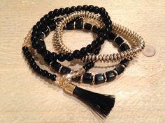 Een kwastje aan een kralenarmband met goud en zwart tinten. Makkelijk over de hand aan te doen door elastiek.