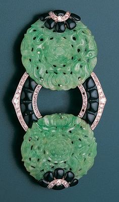An art deco enamel, jade and diamond devant de corsage, French, circa 1925. The central annular motif decorated with black enamel plaques within borders of millegrain-set brilliant, single and rose-cut diamonds, between carved jade rosettes, each with applied black enamel and millegrain-set rose-cut diamond flower head finials, French assay marks. #ArtDeco