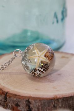 Tiny shells and starfish gently float in real sand in this 25mm resin orb necklace. Bits of real silver flake and glitter add a bit of gorgeous magic as well! This necklace comes on your choice length of Silver plated chain. If you are an ocean lover, this is a magical little world that will belong to only you! Each necklace will have slight variations but each will be uniquely beautiful!  Perfect for the sea siren or mermaid in your life  Be sure to like my facebook page…