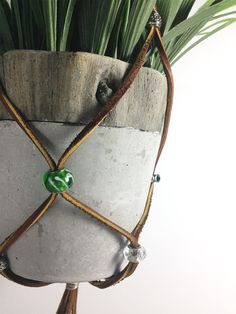 Beautiful and original adjustable plant hanger made from leather lace, glass beads and metal beads. This is like macrame without all the knots! This hanging planter would make a wonderful gift for the indoor gardener in your life.  Flowerups.com