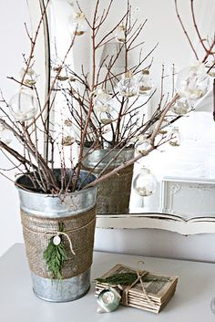 Bare branches in a pail are hung with ornaments - burlap with greens