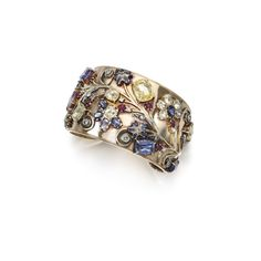 Gem set and diamond cuff bracelet, 1940s The cuff bracelet with a stylised floral motif, set with cushion-shaped and oval multi-coloured sapphires and single-cut diamonds, inner circumference approximately 165mm.