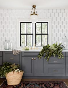Charcoal gray laundry room cabinets donning brash brass hardware are topped with a white quartz countertop holding a sink with an antique brass vintage faucet beneath windows framed by white quartz backsplash tiles. Grey Laundry Rooms, Laundry Room Cabinets, Grey Cabinets, Cupboards, Coloured Kitchen Cabinets, Shaker Cabinets, Office Cabinets, Home Renovation, Casa Magnolia