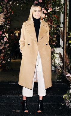 Taylor Schilling wears a turtleneck, white culottes, camel coat, and peep-toe booties