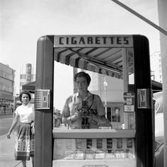 """Vivian Maier Self Portrait - Maier has used the window of a cigarette kiosk as an already prepared frame in which she has placed herself to take her photograph. I love Maier's style of using places she finds as the """"set"""" for her photograph, with it already being set up rather than her constructing it herself. Maier's photographs have an element of candid photography about them. In this photograph she has captured someone else walking past, oblivious to the fact they are in her photograph."""
