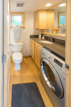 The bathroom in this tiny house has a flush toilet, a full 5' tub/shower combo, and room for a washer/dryer combo.