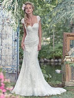 Maggie Sottero - RITA, Simplistic elegance is found in this lace fit and flare wedding dress, sprinkled with glittering Swarovski crystals. Finished with sweetheart neckline and covered buttons over zipper and inner elastic closure. Detachable beaded lace cap-sleeves sold separately.