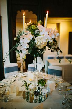 Tall elegant Crystal Candelabras topped with floral magnificence and surrounded…