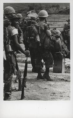 "Marines Wait to Board a Transport Helicopter, 1968 ""That's the Spirit: A Leatherneck of the 3d Marines carries a small US flag while waiting to board a transport helicopter heading for a fire support base in Operation Taylor Common west of An Hoa (official USMC photo by Lance Corporal E. E. Hildreth)."" From the Jonathan Abel Collection (COLL/3611), Marine Corps Archives & Special Collections."
