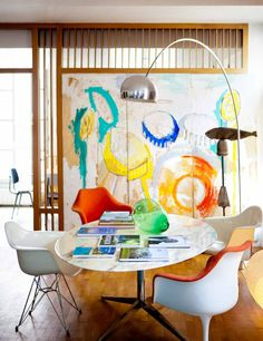 Vibrant modern meeting space: Knoll Table Desk, Saarinen Tulips three ways, and Eames Plastic Shell, Arco lamp.